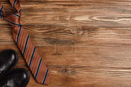 Photo for Top view of mens shoes, elegant striped tie on wooden background - Royalty Free Image