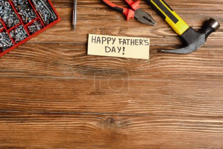 Photo for Top view of greeting card with handwritten lettering happy fathers day, hammer, pliers, screwdriver, nuts and bolts on wooden background - Royalty Free Image