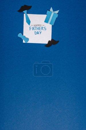 Photo pour Vue du dessus de la carte de vœux avec lettrage heureux jour des pères et papier artisanat éléments de décoration créatifs sur fond bleu - image libre de droit