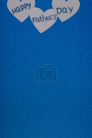 Photo pour Vue du dessus du papier gris coeurs fabriqués avec lettrage heureux jour des pères sur fond bleu - image libre de droit