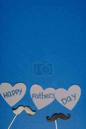Photo for Top view of decorative black mustache and paper cutted grey hearts with lettering happy fathers day on blue background - Royalty Free Image