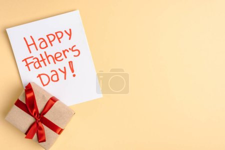 top view of gift box with red bow and greeting card with lettering happy fathers day on beige background