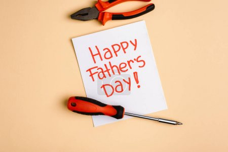 Photo for Top view of screwdriver, pliers and greeting card with lettering happy fathers day on beige background - Royalty Free Image