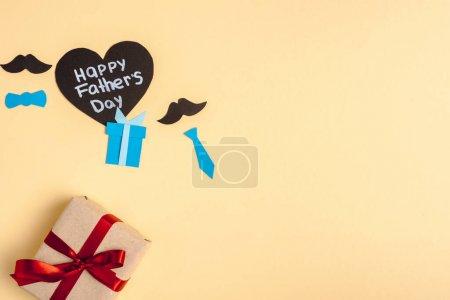 Foto de Vista superior de la caja de regalo, elementos decorativos de papel y tarjeta de felicitación en forma de corazón con carta de padres felices día en segundo plano beige. - Imagen libre de derechos
