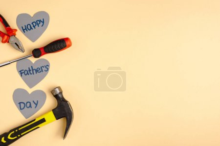 Photo for Top view of hammer, screwdriver, pliers and paper hearts with lettering happy fathers day on beige background - Royalty Free Image