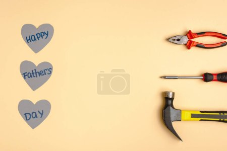 Photo for Flat lay with hammer, screwdriver, pliers and paper hearts with lettering happy fathers day on beige background - Royalty Free Image