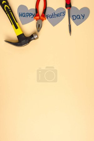 Photo for Top view of hammer, screwdriver, pliers and grey paper hearts with lettering happy fathers day on beige background - Royalty Free Image