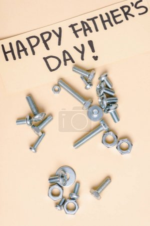 Photo for Top view of metal nuts and bolts and beige greeting card with lettering happy fathers day on beige background - Royalty Free Image