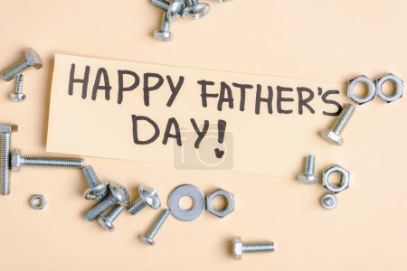 Photo for Top view of metal nuts and bolts and beige greeting card with handwritten lettering happy fathers day on beige background - Royalty Free Image