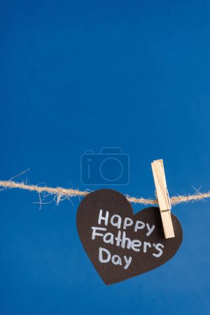 Photo for Black paper heart with white lettering happy fathers day hanging on rope with clothespins isolated on blue - Royalty Free Image