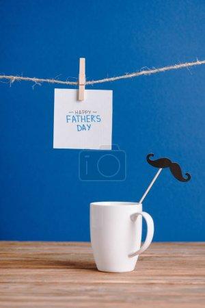 Photo pour Foyer sélectif de tasse blanche avec papier décoratif fausse moustache et carte de vœux blanche avec lettrage heureux jour des pères isolé sur bleu - image libre de droit