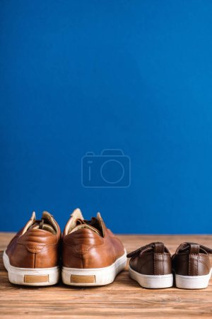 Photo for Mens and childrens casual beige shoes on wooden surface isolated on blue, fathers day concept - Royalty Free Image