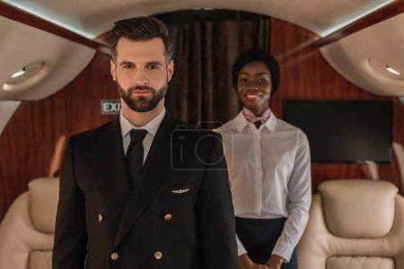 Foto de Enfoque selectivo de piloto seguro de sí mismo y sonriente azafata afroamericana mirando a la cámara en avión privado - Imagen libre de derechos