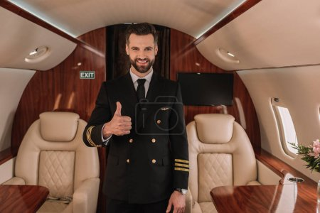 Photo for Handsome pilot of private jet showing thumb up while smiling at camera - Royalty Free Image