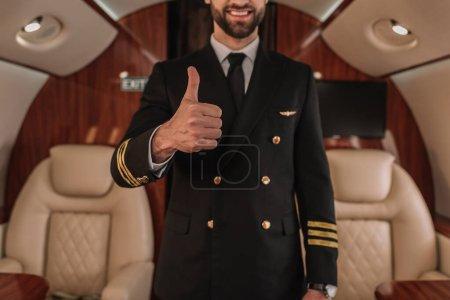 Photo pour Vue recadrée du pilote souriant d'un jet privé montrant le pouce levé - image libre de droit