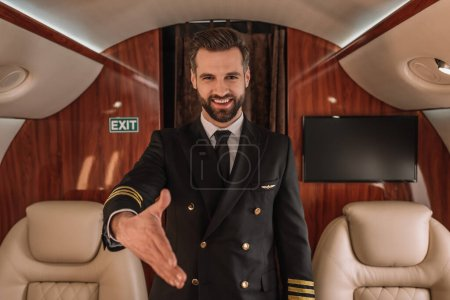 Photo for Handsome pilot smiling at camera while standing with outstretched hand - Royalty Free Image