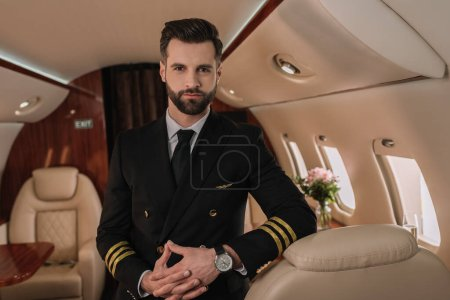 Photo for Handsome, confident pilot in uniform looking at camera while standing in private jet - Royalty Free Image