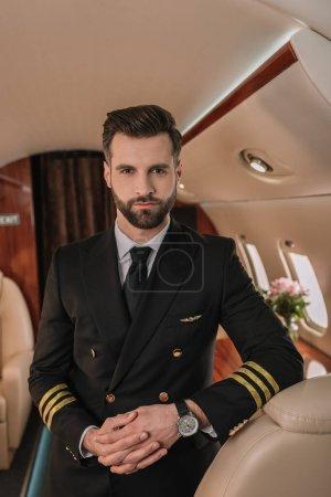Foto de Piloto guapo y seguro de sí mismo mirando a la cámara mientras está de pie en el avión - Imagen libre de derechos