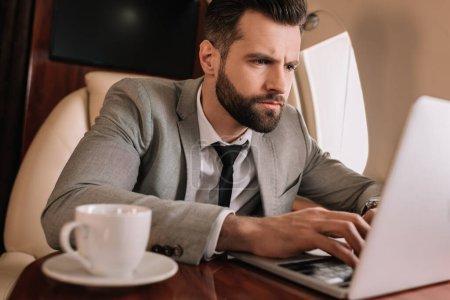 Photo pour Concentration sélective de l'homme d'affaires concentré travaillant sur ordinateur portable en avion privé - image libre de droit
