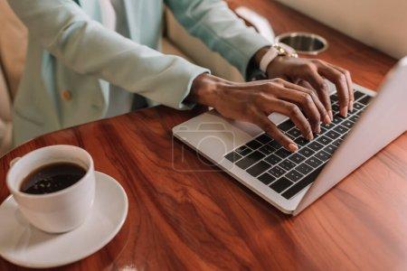 vista recortada de la mujer de negocios afroamericana escribiendo en el ordenador portátil cerca de la taza de café