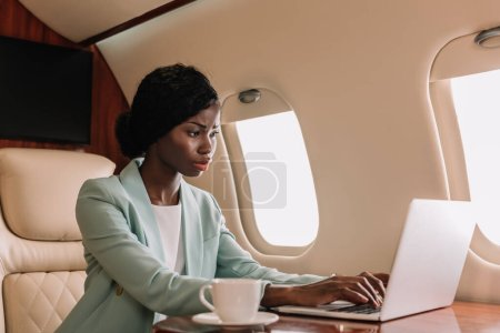 attractive, confident african american businesswoman working on laptop in private jet