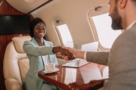 Photo pour Foyer sélectif de sourire femme d'affaires afro-américaine serrant la main avec un homme d'affaires dans l'avion - image libre de droit