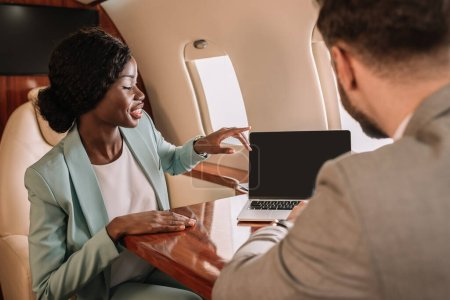 back view of businessman near smiling african american businesswoman pointing with finger and laptop with blank screen