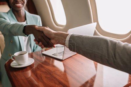 Foto de Vistas rotas de afriquísimas empresarias afriamericanas estrechando la mano con hombres de negocios en avión. - Imagen libre de derechos