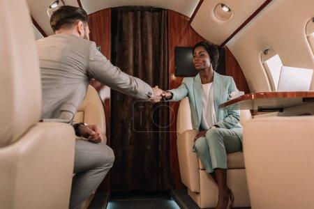 Foto de Enfoque selectivo de dos empresarios multiculturales estrechando la mano mientras viajan en avión privado - Imagen libre de derechos
