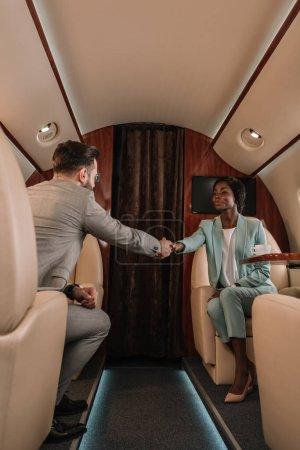 Photo pour Deux hommes d'affaires multiculturels serrant la main tout en voyageant en jet privé - image libre de droit