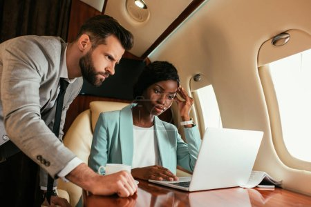 two multicultural businesspeople looking at laptop while traveling in private jet