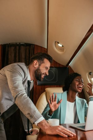Photo for Smiling businessman standing near excited african american businesswoman waving hand while having video call in private jet - Royalty Free Image