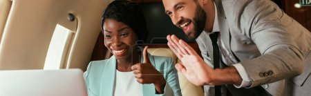 Photo for Panoramic shot of cheerful businessman waving hand and african american businesswoman showing thumb up during video call in private plane - Royalty Free Image