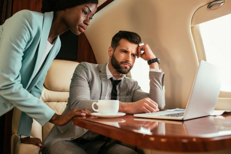 serious businessman and african american businesswoman looking at laptop in private jet