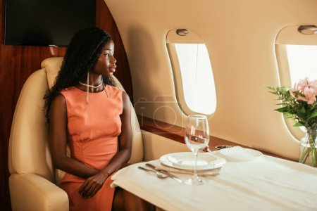 Photo for Attractive, elegant african american woman looking in porthole of private plane while sitting at served table - Royalty Free Image