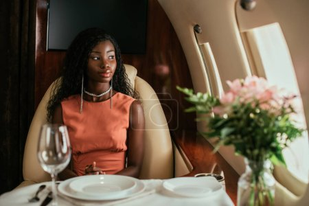 selective focus of dreamy african american woman sitting at served table in private plane