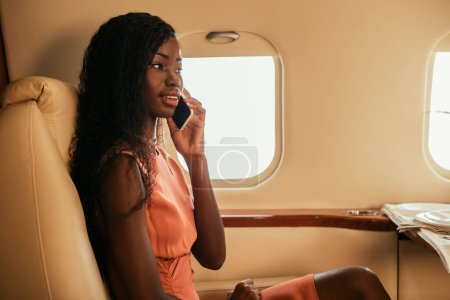 Photo for Smiling african american woman talking on smartphone while traveling in private plane - Royalty Free Image