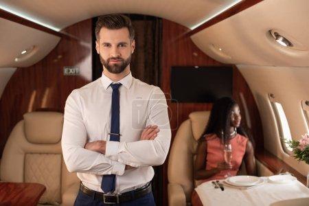Foto de Apuesto administrador de aire con brazos cruzados mirando a la cámara cerca de elegante mujer afroamericana en avión privado - Imagen libre de derechos