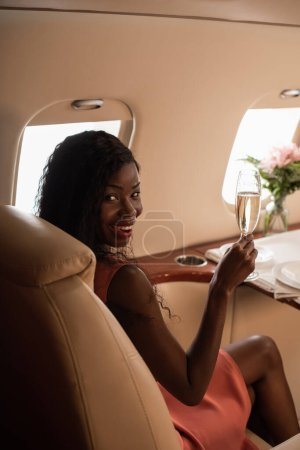 Photo for Attractive african american woman travelling in private jet, holding glass of champagne and smiling at camera - Royalty Free Image