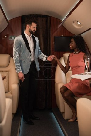 Photo for Smiling, elegant interracial couple holding hands and looking at each other in private jet - Royalty Free Image
