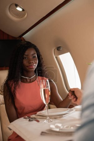 cropped view of man holding hands with elegant african american woman in private plane