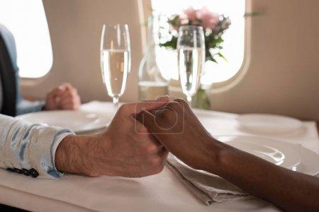Foto de Vistas rotas de pareja interracial con las manos cerca de copas de champán en la mesa servida en chorro privado. - Imagen libre de derechos