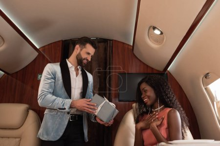 handsome, elegant man presenting gift box to suprised african american woman in private plane