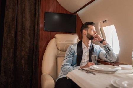 Photo pour Bel homme rêveur regardant dans hublot alors qu'il était assis à table dans un avion privé - image libre de droit