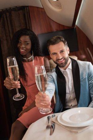 Photo pour Heureux, élégant couple interracial tenant des verres de champagne tout en regardant la caméra en jet privé - image libre de droit