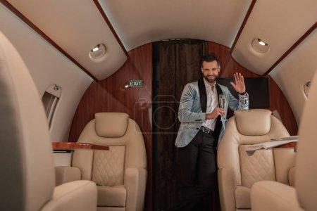 Foto de Enfoque selectivo de elegante, hombre guapo agitando la mano y sosteniendo la copa de champán en avión privado - Imagen libre de derechos