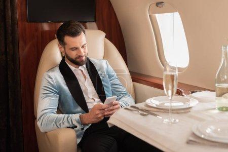 Foto de Hombre elegante charlando en el teléfono inteligente mientras está sentado en la mesa servida en jet privado - Imagen libre de derechos