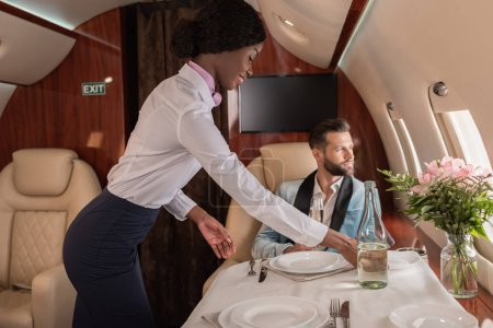Photo for Smiling, pretty african american stewardess setting table in private jet near elegant man - Royalty Free Image