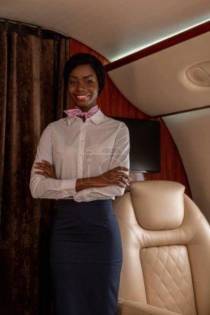 Photo pour Belle hôtesse afro-américaine souriante debout avec les bras croisés en jet privé et regardant la caméra - image libre de droit