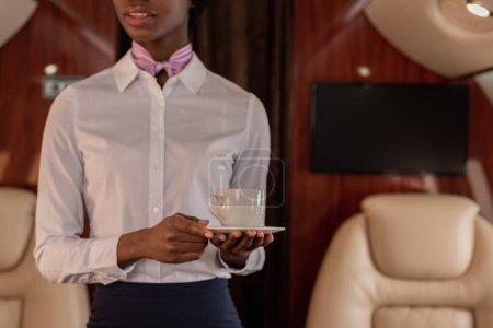 Photo pour Vue recadrée de l'hôtesse afro-américaine tenant une tasse de café en jet privé - image libre de droit